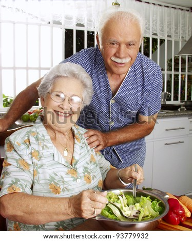 Happy senior couple preparing vegetable salad in the kitchen. Grandparents at kitchen preparing vegetable salad.