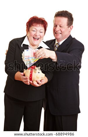 Happy senior couple putting Euro money in a piggy bank