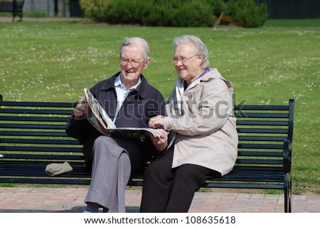 Happy senior couple reading a newspaper on a park bench