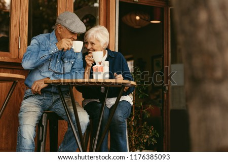 Happy senior couple sitting at coffee shop and talking. Elderly man and woman relaxing at cafe and having coffee.