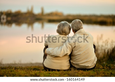 Happy senior couple sitting in summer near lake during sunset