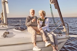 Happy senior couple sitting on the side of sail boat or yacht deck floating in sea. Man and woman drinking wine or champagne and laughing