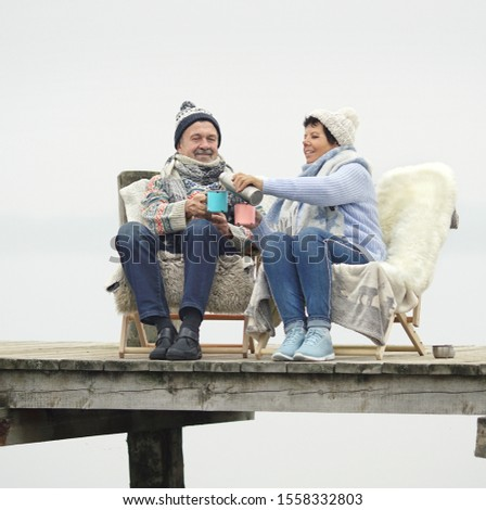 happy senior couple sitting on wooden jetty and enjoy the winter day with hot tea stock photo