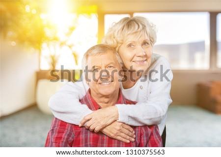 Happy senior couple smiling on background