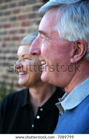 Happy Senior Couple smiling outside in front of their house