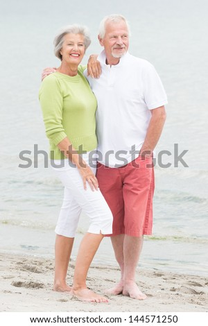 Happy senior couple standing at the beach