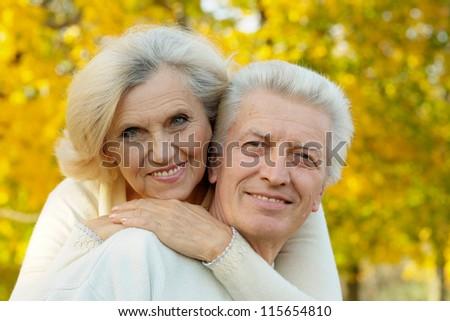 happy senior couple standing in autumn park