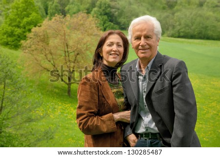 Happy senior couple standing on a meadow, enjoying themselves and smiling into the camera