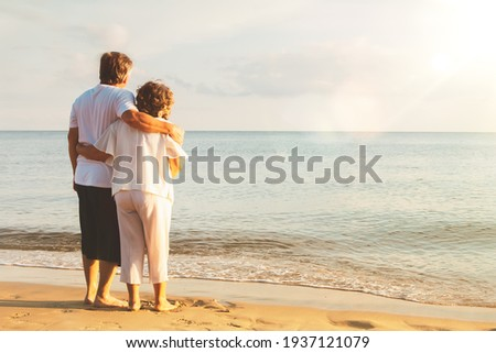 Happy senior couple summer beach : Back view together romance of an elderly couple on a quiet beach : Retired Asian couple in an everlasting relationship, they both look to the sea with their bond.