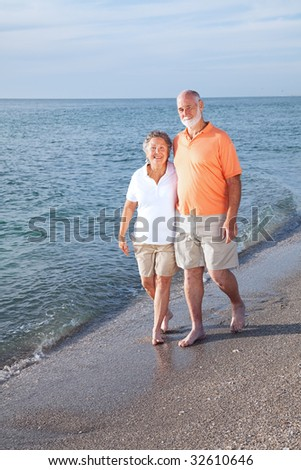 Happy senior couple take a stroll on a beautiful tropical beach.