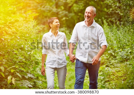 Happy senior couple taking a walk in summer in a forest