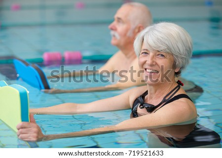 happy senior couple taking swimming lessons