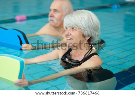 happy senior couple taking swimming lessons #736617466