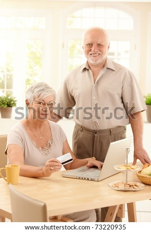 Happy senior couple using laptop computer, purchasing on Internet with credit card at home, smiling at camera.?