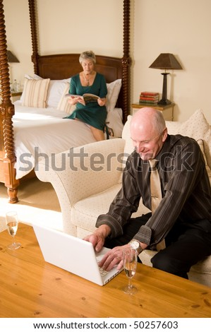 Happy senior couple using laptop in luxurious hotel bedroom suite