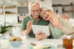 Happy senior couple using touchpad and waving while greeting someone during a video chat at home.