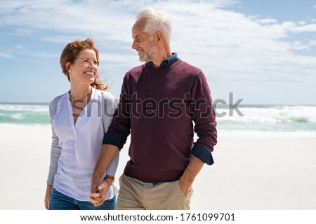 Happy senior couple walking on the beach in a sunny day. Smiling mature couple looking at each other on beach during sunset with copy space. Retired man in love with his wife relaxing during vacation. Сток-фото ©