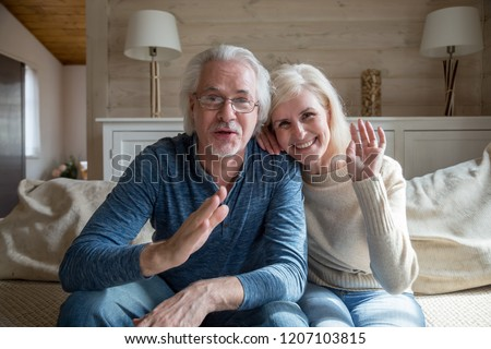 Happy senior couple wave having video call on laptop talking with relatives, smiling aged husband and wife sit on couch at home communicating via skype using computer. Elderly and technology concept