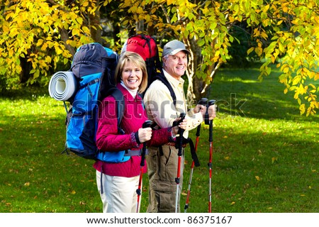 Happy senior couple with backpacks and trekking poles.