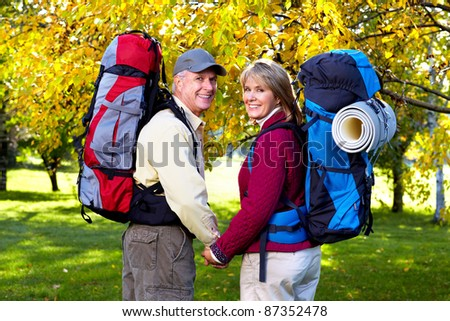 Happy senior couple with backpacks in the park.