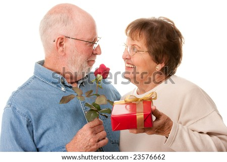 Happy Senior Couple with Gift and Red Rose Isolated on a White Background. - stock photo