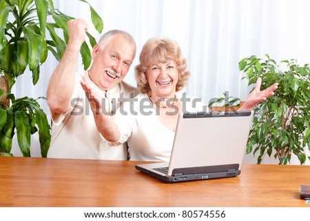 Happy senior couple with laptop at home.