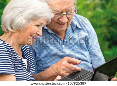 Happy senior couple with  laptop, outdoors