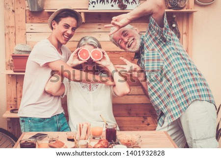 Happy senior couple with teenager nephew have fun at breakfast. Craziness and laughs. Wood on background and on table.Three people enjoying life. Food and drink #1401932828