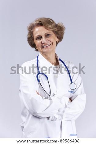 Happy senior doctor smiling (isolated on gray) - stock photo
