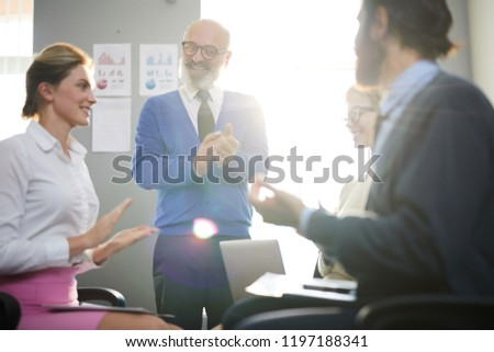 Happy senior employer and his young subordinates applauding to their success after business conference