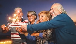 Happy senior family celebrating with sparkler fireworks at home party - Elderly people lifestyle and holidays concept