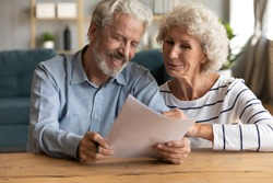 Happy senior family couple looking at paper sheet, reading letter with pleasant news. Smiling middle aged husband and wife holding correspondence mail or medical insurance contract together at home.