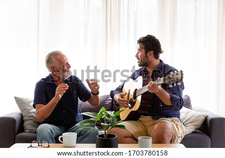 Happy Senior Father sing a song and Adult Son playing guitar on the sofa at home. Elderly father and son spending time together at home.