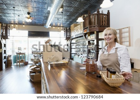 Happy senior female spice merchant standing at counter while looking away in store