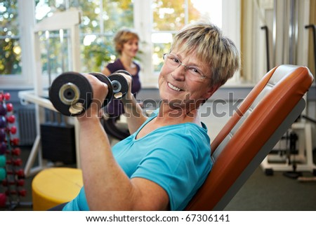 Happy senior female with dumbbells in gym