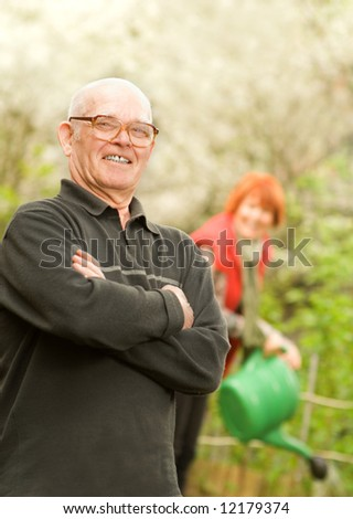 Happy senior gardener and woman watering plants on a background