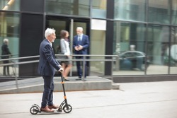 Happy senior gray-haired businessman commuting to work on a kick scooter. Riding on a sidewalk in front of an office building. Two people talking in the background, blurred