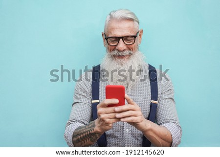 Happy senior hipster man using mobile phone outdoors in the city - Focus on face