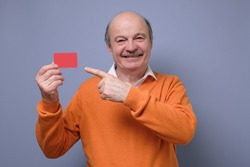 Happy senior hispanic bald man advertising bonus card pointing on it with finger smiling at camera. Guy going to pay by credit card, doing shopping