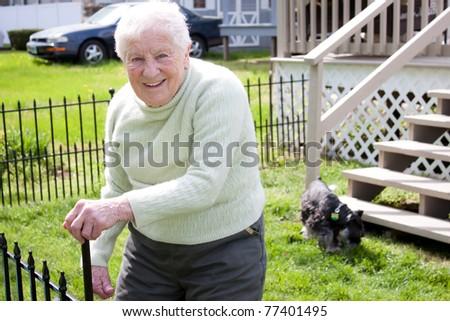 Happy senior lady in backyard with her dog