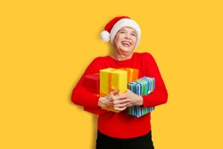 Happy senior lady in Santa red hat with Christmas presents looking at camera and smiling posing on a yellow background.  Christmas time.