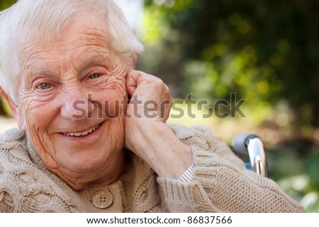 Happy senior lady in wheelchair smiling outside