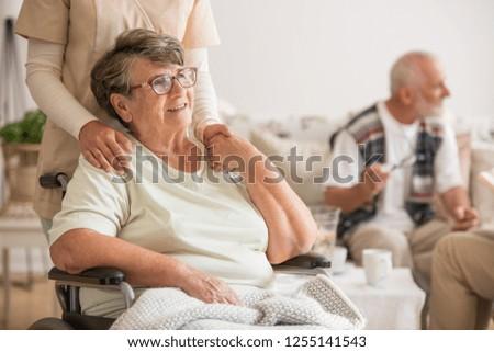 Happy senior lady sitting at wheelchair in nursing home for elderly #1255141543