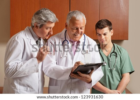 Happy senior male doctor writing on clipboard while colleagues standing besides
