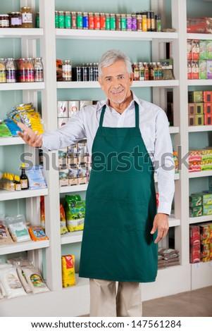Happy senior male store owner gesturing in supermarket - stock photo
