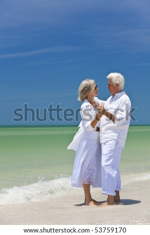 Happy senior man and woman couple dancing and holding hands on a deserted tropical beach with bright clear blue sky