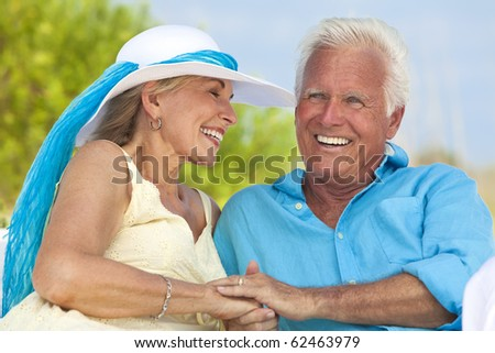 Happy senior man and woman couple having fun together holding hands and laughing on a deserted tropical beach.