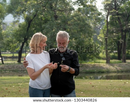 Happy senior man and woman couple in a park on a sunny day. relax in the forest spring summer time. free time, lifestyle retirement grandparents concept.