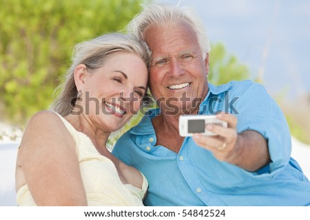 Happy senior man and woman couple laughing and taking photographs with a cell phone on a tropical beach with bright clear blue sky