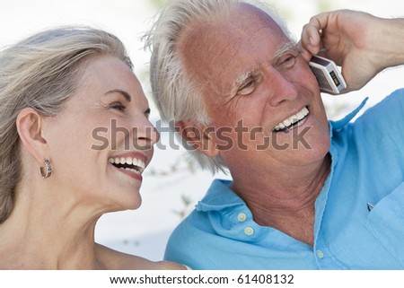 Happy senior man and woman couple laughing while talking on a mobile cell phone
